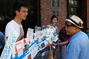 "CAAAV volunteer shares ""History of Organizing"" timeline at CTU's Take Back Chinatown event."